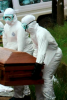 Photo from film: People in protective gear carrying coffin