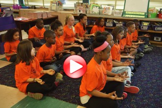 Still image from video of students practicing mindfulness