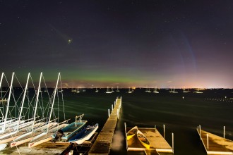 """Colorful bands of the Aurora Borealis, or """"northern lights,"""" glow in the nighttime sky above boats in Lake Mendota mooring field near the Memorial Union Terrace at the University of Wisconsin-Madison during a strong solar storm in the northern hemisphere at 1:28 a.m. on June 23, 2015. The solar storm, a phenomenon rarely visible this far south above the U.S., registered 8 on the Kp scale for planetary geomagnetic activity. (Photo by Jeff Miller/UW-Madison)"""