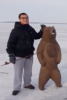 Photo: Man standing with wooden bear