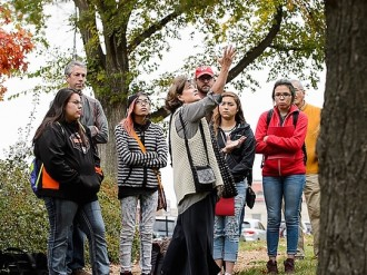 Patty Loew (wearing white sweater vest at center), professor of life sciences communication and a Bad River tribal member, talks about cultural history and digital storytelling with nine high school students from Wisconsin's Ho-Chunk Nation as the youth gathered near a Native American effigy mound and the Tree of Peace on Observatory Hill at the University of Wisconsin-Madison during autumn on Oct. 23, 2015. The UW Arboretum's Earth Partnership Program and UW-Madison's Nelson Institute for Environmental Studies hosted the group's one-day visit to campus. (Photo by Jeff Miller/UW-Madison)