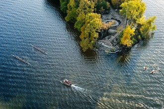 Members of the Wisconsin men's rowing team plus a few kayakers paddle along Lake Mendota past the tip of Picnic Point as pictured in an aerial view of the University of Wisconsin-Madison campus during an autumn sunset on Oct. 5, 2011. The tip of Picnic Point is being renovated to repair an eroding shoreline and construct terraced-steps with a clearer view of the city skyline. The photograph was made from a helicopter looking south. (Photo by Jeff Miller/UW-Madison)
