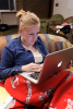 Photo: Student with earbuds working on laptop