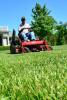 Photo: Man on riding lawn mower in yard