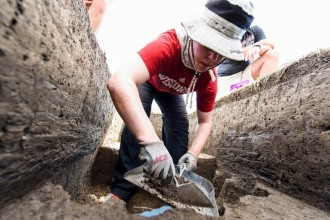 Photo: Student digging with trowel