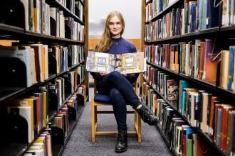 Photo: Elise Schmke sitting in between library shelves
