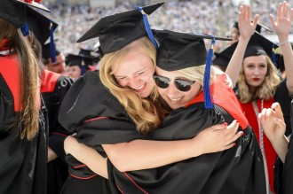 Photo: Two students in caps and gowns embracing