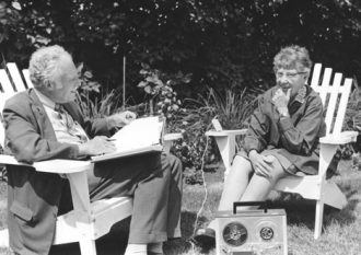 Photo: Fred Cassidy and unidentified woman sitting outdoors with tape recorder