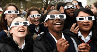 Photo: Smiling children looking through eclipse-viewing glasses